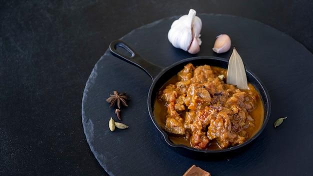 Tradycyjne indyjskie curry z wołowiny podawane z odlewu z żelaza kuchnia świata czarne tło łupkowe
