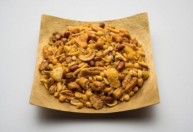 Tradycyjne indyjskie danie smażone w głębokim tłuszczu - chivda lub mieszanka lub farsan lub farsaan z gramowej mąki zmieszanej z suszonymi owocami podawane w misce lub talerzu