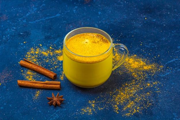Tradycyjne indyjskie mleko kurkumowe w szklanym kubku z gwiazdką anyżu i cynamonem