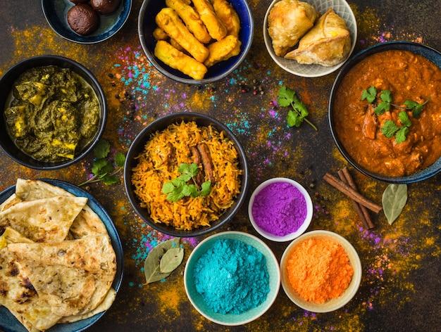 Tradycyjne indyjskie potrawy, proszkowe kolory holi, rustykalne tło.