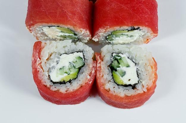 Tradycyjne japońskie jedzenie. roladki sushi ze świeżym kawiorem z awokado i serkiem śmietankowym oraz wędzonym łososiem