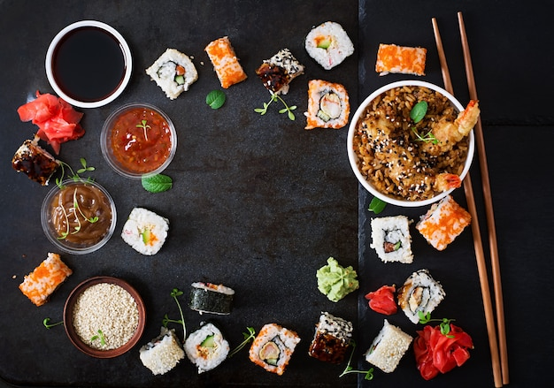 Tradycyjne japońskie jedzenie - sushi, bułki, ryż z krewetkami i sosem na ciemnym tle. widok z góry