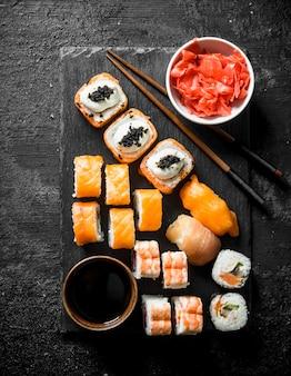 Tradycyjne japońskie rolki sushi z imbirem i sosem sojowym na czarnej kamiennej desce. na czarnym rustykalnym