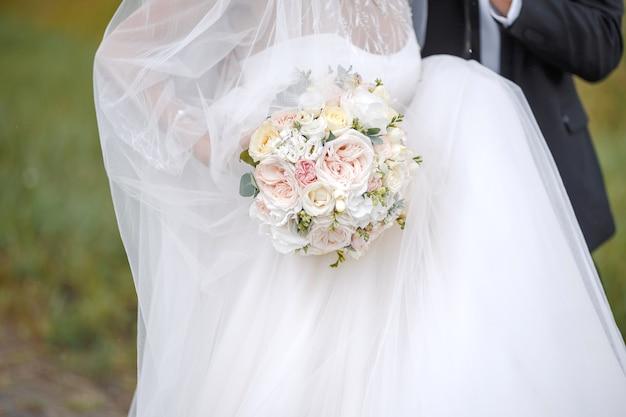 Tradycyjne jasnoróżowe i białe róże ułożone w bukiet ślubnyromantyczna dekoracja uroczystości