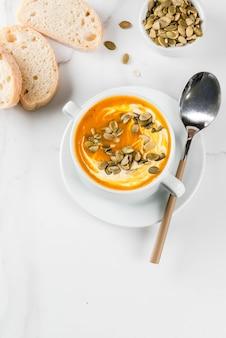 Tradycyjne jesienne i zimowe dania, gorąca i pikantna zupa dyniowa z pestkami dyni, śmietana i świeżo upieczona bagietka, na białym marmurowym stole, widok z góry