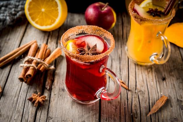 Tradycyjne jesienne i zimowe napoje i koktajle. biało-czerwona jesienna ostra sangria z anyżem, cynamonem, jabłkiem, pomarańczą, winem. w szklanych kubkach stary rustykalny drewniany stół. przestrzeń kopiowania selektywnej ostrości