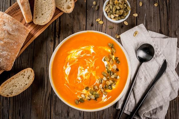 Tradycyjne jesienne i zimowe potrawy, gorąca i pikantna zupa dyniowa z pestkami dyni, śmietana i świeżo upieczona bagietka, na starym rustykalnym drewnianym stole, widok z góry