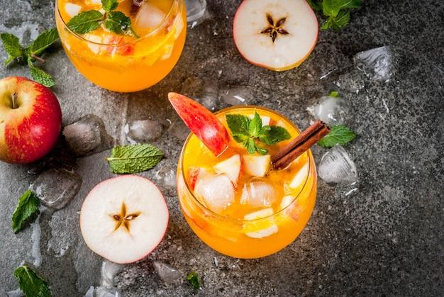 Tradycyjne jesienne napoje, koktajle z jabłkowego cydru z miętą, cynamonem i lodem. na czarny kamienny stół, widok z góry copyspace