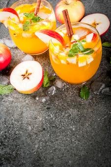 Tradycyjne jesienne napoje, koktajle z jabłkowego cydru z miętą, cynamonem i lodem. na czarnym kamiennym stole, miejsce