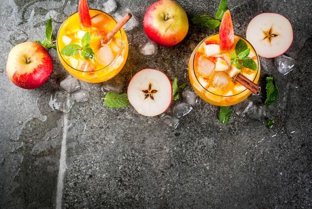 Tradycyjne jesienne napoje, koktajle z jabłkowego cydru z miętą, cynamonem i lodem. na czarnym kamiennym stole skopiuj widok z góry miejsca