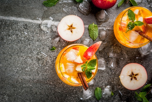Tradycyjne jesienne napoje, koktajle z jabłkowego cydru z miętą, cynamonem i lodem. na czarnym kamiennym stole widok z góry