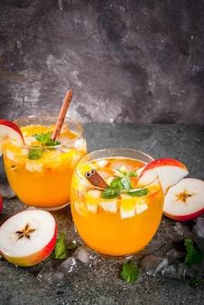 Tradycyjne jesienne napoje, koktajle z jabłkowego cydru z miętą, cynamonem i lodem. na czarnym kamiennym stole
