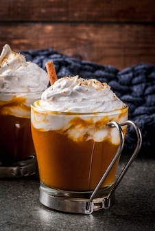 Tradycyjne jesienne potrawy. halloween, święto dziękczynienia. gorąca i pikantna aromatyczna latte dyniowa z cynamonem na czarnym kamiennym stole, z kocem. copyspace