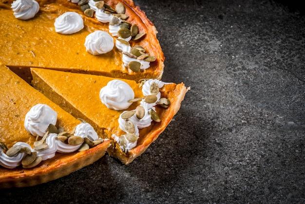 Tradycyjne jesienne potrawy. halloween, święto dziękczynienia. krojone pikantne ciasto dyniowe z bitą śmietaną i pestkami dyni na czarnym kamiennym stole. copyspace