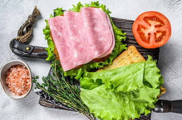 Tradycyjne kanapki klubowe z szynką z indyka, serem, pomidorami i sałatą. białe tło. widok z góry.