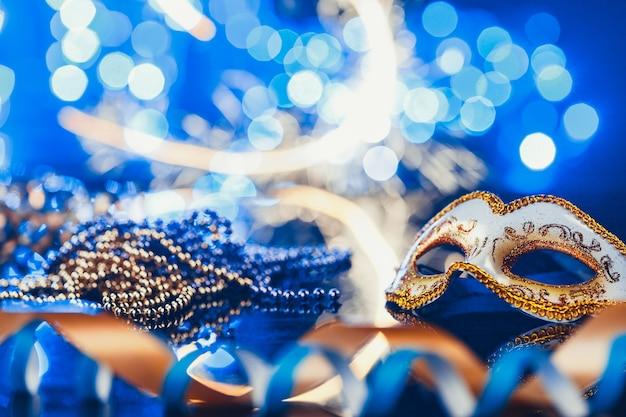 Tradycyjne kobiece karnawałowe maski weneckie na niebieskim tle bokeh. maskarada, wenecja, mardi gras, koncepcja festiwalu w brazylii