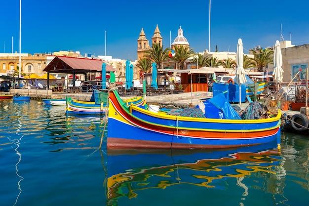 Tradycyjne kolorowe łodzie luzzu w porcie w śródziemnomorskiej wiosce rybackiej marsaxlokk, malta