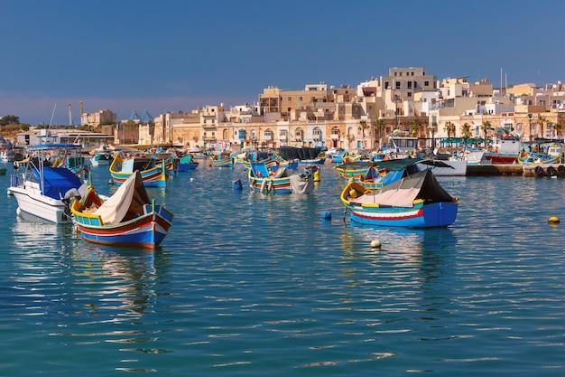 Tradycyjne kolorowe łodzie o oczach luzzu w porcie w śródziemnomorskiej wiosce rybackiej marsaxlokk, malta