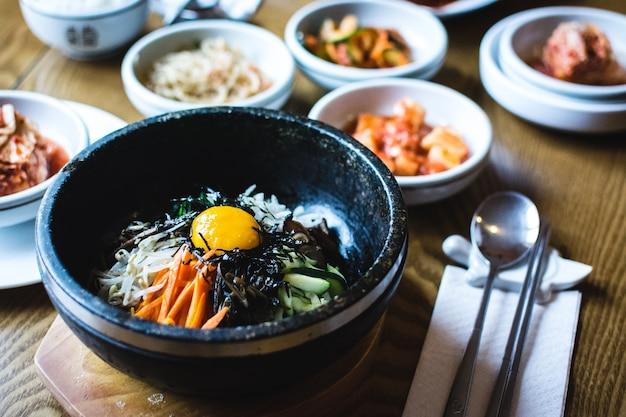 Tradycyjne koreańskie warzywa bibimbap z surowym żółtkiem jaja