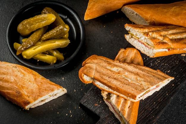Tradycyjne kubańskie jedzenie, przekąska, impreza. kubańska kanapka z bagietki z szynką, wieprzowiną, serem, piklami. na czarnym stole copyspace