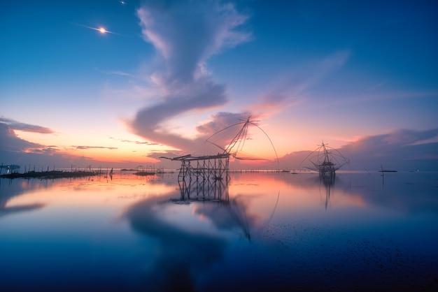 Tradycyjne kwadratowe kabaretki o wschodzie słońca w kanale pakpra, phatthalung, tajlandia
