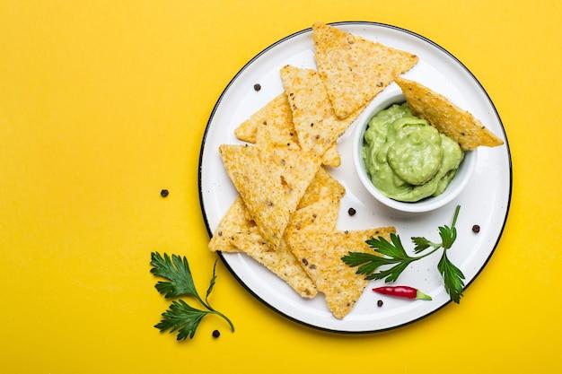 Tradycyjne latynoamerykańskie guacamole z nachos z chipsami kukurydzianymi na żółtym tle.
