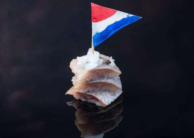 Tradycyjne lokalne jedzenie. kawałki śledzia na ciemnym tle z flagą holandii.