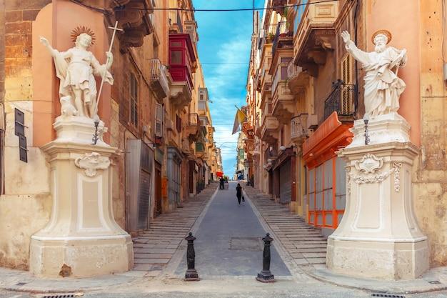 Tradycyjne maltańskie schody uliczne z narożnikami domów ozdobionych figurami świętych jana i pawła oraz budynek z kolorowymi balkonami w valletcie, stolicy malty