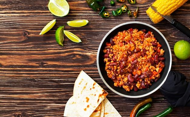 Tradycyjne meksykańskie chili con carne podawane na rustykalnym drewnianym stole na patelni z kukurydzą, meksykańskim chlebem z tortilli, limonką i jalapeño. widok z góry.