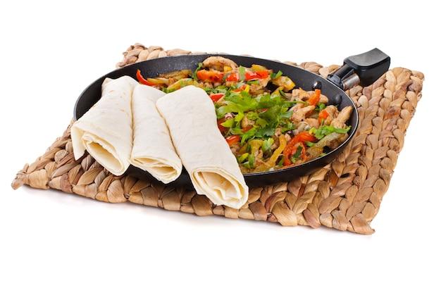 Tradycyjne meksykańskie fajitas wołowe z tortillami na białym tle