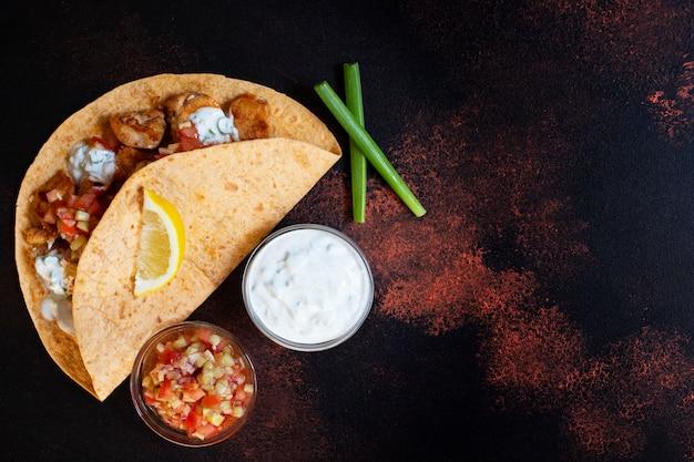 Tradycyjne meksykańskie fajitas z kurczakiem i warzywami, podawane w tortilli z białym i czerwonym sosem, cytryną i świeżą zieloną cebulą. widok z góry. ciemne tło. skopiuj miejsce