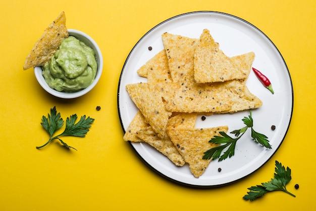 Tradycyjne meksykańskie jedzenie guacamole z chipsami kukurydzianymi na żółtym tle.