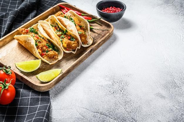 Tradycyjne meksykańskie tacos z pietruszką, serem i papryczkami chili. białe tło