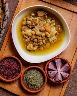 Tradycyjne naczynie szkoda na drewnianej desce baranina grochu sumakh kartoflanej cebuli odgórnego widok
