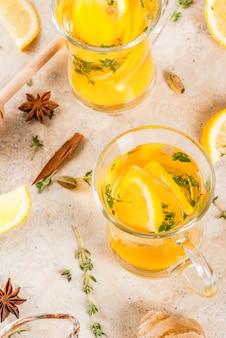Tradycyjne napoje na jesień i zimę. rozgrzewająca gorąca herbata z cytryną, imbirem, przyprawami (anyż, cynamon) i ziołami (tymianek), copyspace