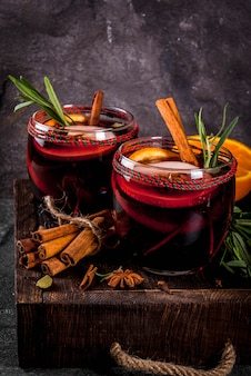 Tradycyjne napoje zimowe i jesienne koktajle bożonarodzeniowe i dziękczynne grzane wino z pomarańczowym jabłkiem rozmarynem cynamonem i przyprawami na ciemnym tle kamienia