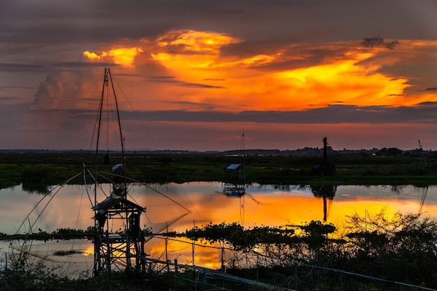 Tradycyjne narzędzie wędkarskie lub bambusowa pułapka na ryby w świetle zachodzącego słońca, sylwetka krajobrazu.
