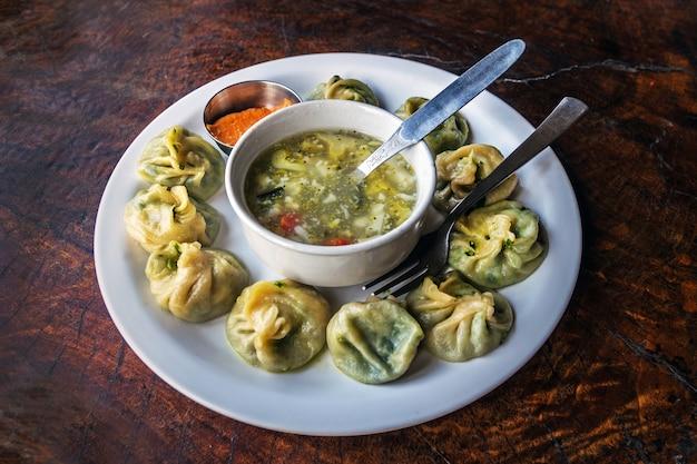 Tradycyjne nepalskie pierożki momos podawane z pomidorowym chatni i gorącą zupą