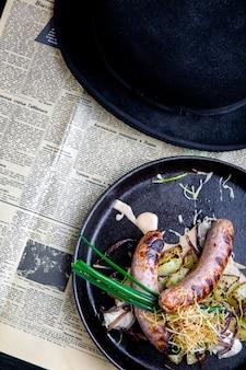 Tradycyjne niemieckie kiełbaski z ziemniakami podawane na patelni. danie w restauracji. widok z góry