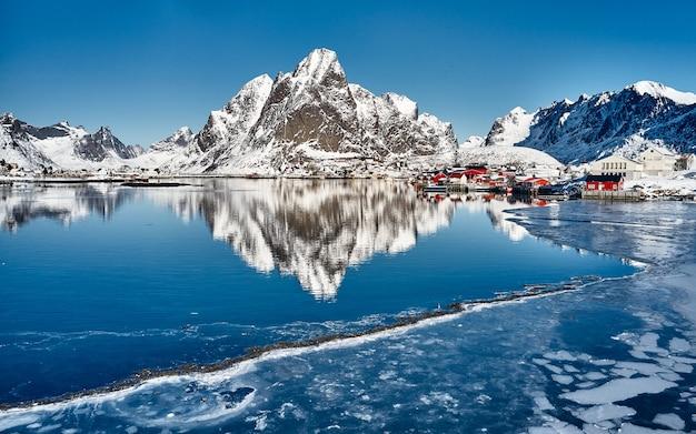 Tradycyjne norweskie chaty rybackie, rorbu, na pół zamarzniętym morzu. ogromne góry w tle.