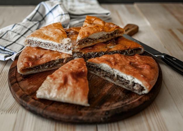 Tradycyjne osetyjskie pasztety mięsne z wołowiną, na drewnianym stole. styl rustykalny, bliska, selektywna ostrość