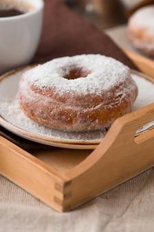 Tradycyjne pączki na drewnie. smaczne pączki z cukrem pudrem