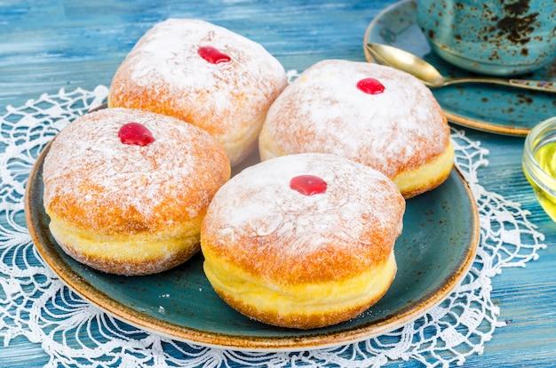 Tradycyjne pączki z cukrem pudrem i dżemem. pojęcie żydowskiego święta chanuka.
