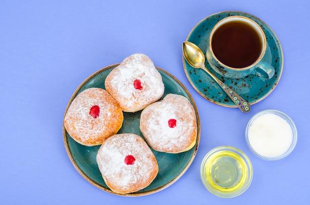 Tradycyjne pączki z cukrem pudrem i dżemem. święto żydowskie chanuka.