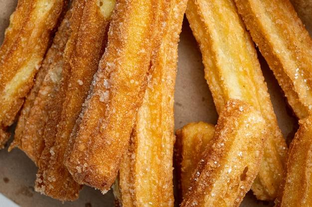 Tradycyjne paluszki churros z cynamonem i cukrem pudrem, widok z góry na płasko