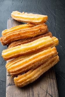 Tradycyjne paluszki churros z zestawem cynamonu i cukru pudru, na czarnym tle