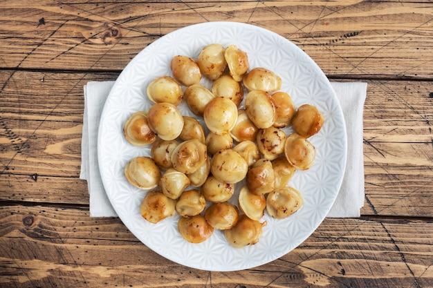 Tradycyjne pelmeni smażone, ravioli, pierogi z mięsem na talerzu, kuchnia rosyjska. drewniany stół rustykalny, miejsce na kopię.