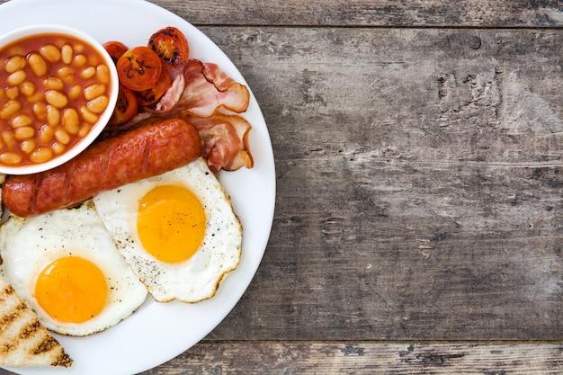 Tradycyjne pełne angielskie śniadanie ze smażonymi jajkami, kiełbasami, fasolą, pieczarkami, grillowanymi pomidorami i boczkiem na drewnianej powierzchni