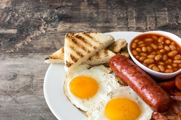 Tradycyjne pełne angielskie śniadanie ze smażonymi jajkami, kiełbasami, fasolą, pieczarkami, grillowanymi pomidorami i boczkiem na drewnianej powierzchni.