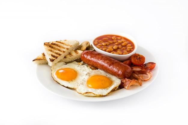 Tradycyjne pełne angielskie śniadanie ze smażonymi jajkami, kiełbasami, fasolą, pieczarkami, grillowanymi pomidorami i boczkiem na na białym na białej powierzchni